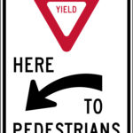 yield here to pedestrians left sign
