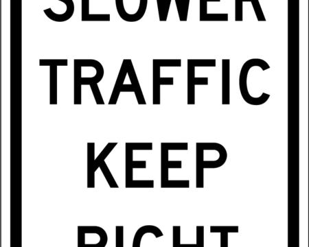 slower traffic keep right white sign